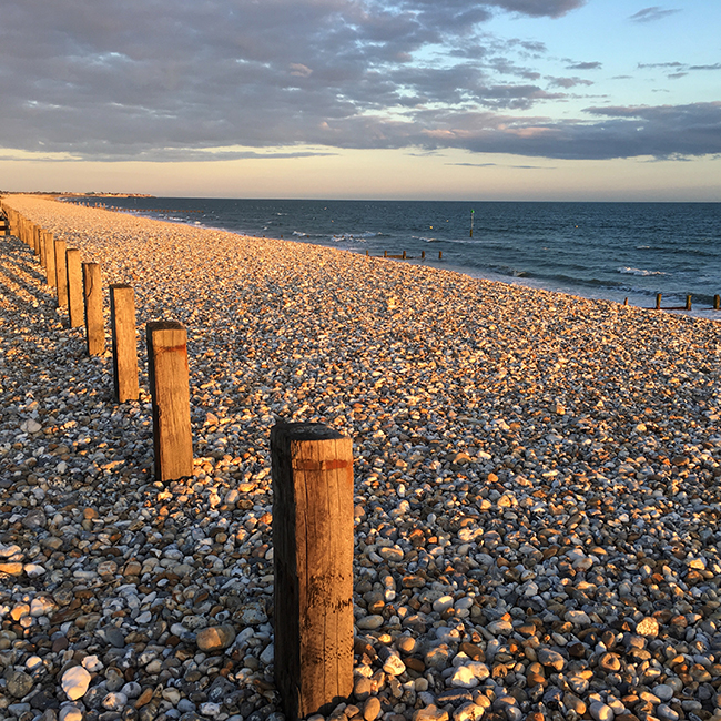 The monotonous texture of the pebbles is balanced by the wooden posts, the sea and the sky.