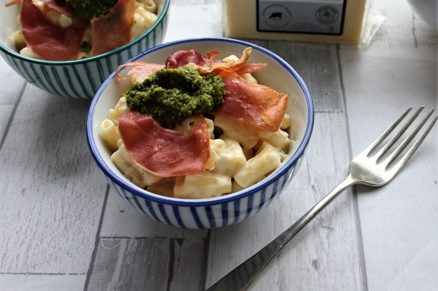 Mac and Cheese with Prosciutto and Pesto -  Serves 6400g macaroni600ml Stephensons Free Range whole milk50g Stephensons butter50g plain flour300g Stephensons Creamy Lancashire cheese, grated30g Parmesan, grated70g prosciutto crudo, grilled until crisp4 tablespoons fresh pesto sauce Method1.  Bring a large pan of salted water to the boil and cook the pasta until al dente. Tip into a colander and leave to drain thoroughly.2.  In a large heavy-bottomed pan, melt the butter. Reduce to a low heat and gradually add the flour, stirring into a paste with a wooden spoon – this is your roux. Cook for 3-4 minutes, stirring continually, until it turns golden in colour and remove it from the heat.3. Pour the milk into a cold saucepan, and whisk the roux into the milk, until blended in.  Return the sauce to the heat and whisk until thickened - about 5-7 minutes.4. Add the Creamy Lancashire and Parmesan cheeses, stir until melted and then mix in the drained macaroni.5. Serve in bowls topped with the grilled prosciutto and a spoonful of pesto.