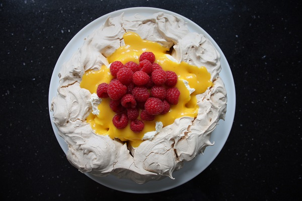 Mango Pavlova - Serves 6-8For the meringue4 egg whites250 grams caster sugar1 teaspoon white wine vinegar1 teaspoon cornflour For the mango curd (makes 2 x 450 ml jars)1 ripe mango (about 450 grams) peeled and choppedJuice and zest of 1 lime125 grams caster sugar125 grams Stephensons butter4 egg yolks, lightly beaten For the filling350 ml Stephensons double cream200 grams fresh raspberries MethodFor the meringue.Heat oven to 150C/130C fan/gas 2. Using a pencil, mark out the circumference of a dinner plate on baking parchment. Whisk the egg whites with a hand mixer until they form stiff peaks, then whisk in the sugar, 1 tablespoon at a time, until the meringue looks glossy. Whisk in the vinegar and cornflour. Spread the meringue inside the circle, creating a crater by making the sides a little higher than the middle. Bake for 1 hr, then turn off the heat and let the Pavlova cool completely inside the oven. Keep in an airtight container for up to 2 days. For the mango curd – makes 2 jars.Sterilize your jars and lids  - either in the dishwasher on a cycle that washes at 55C or hotter, or you can boil in a large pan of boiling water for 10 minutes and stand the jars upside down on fresh kitchen roll to dry. Blitz the mango in a food processor or blender until smooth.  Put the mango, lime zest and juice, sugar, butter and egg yolks into a large heatproof bowl on top of a pan of simmering water.  The bottom of the bowl must not touch the water, otherwise your egg yolks will 'scramble'.  Stir continuously with a wooden spoon until the mixture is thick and coats the back of a spoon- this will take 15-20 minutes, so relax and enjoy the fact that you are making 'artisan' curd that you can't even buy in the shops! It will be slightly runnier than you may be used to, in order for it to pour nicely over the pavlova. Pour the curd into the sterilized jars, cover a seal.  Label the jars when cold and refrigerate for up to 2 weeks.  Once opened, use within 3 days. To assemble.Up to 1 hour before you plan to serve the Pavlova, whip the cream to soft peaks and spoon into the crate you made in meringue base.  Pour over about two-thirds of the jars of mango curd, and top with fresh raspberries.