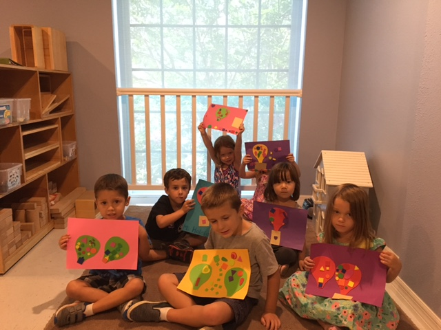 Our youngest campers proudly show off their colorful hot air balloon collages.