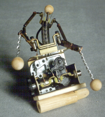 When the music box mechanism is wound-up the penny crankshaft produces a wave type of motion, similar to that of the balance mechanism, so the miniature automaton figure will have a rhythmic side-to-side movement.