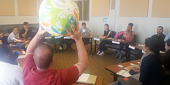 Students prepared for an in-depth discussion about sustainability by answering questions on a beach ball that was tossed among everyone sitting in the circle.