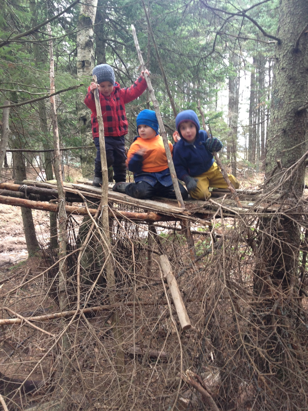 These children are enjoying pretending they are pirates as they climb and balance on the roof of a forest fort.