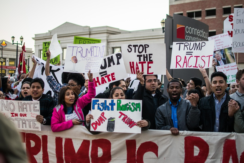 Protesters stand together in unity protesting Trump's proposed immigration reforms and the racism he represents to them.