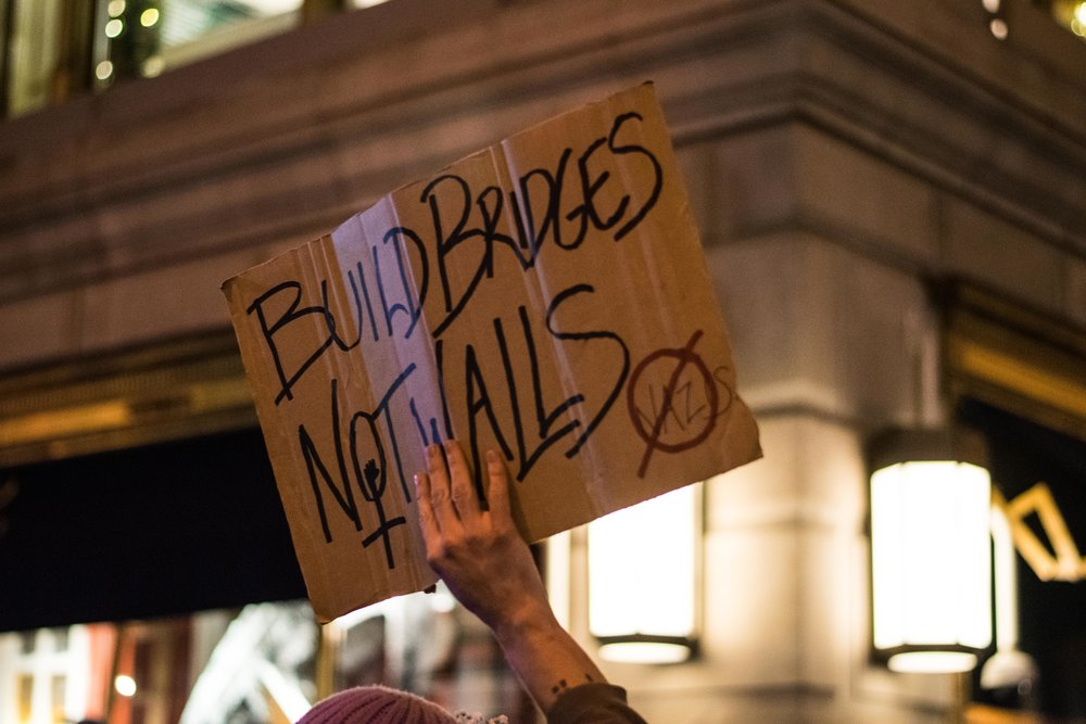 2016-NYC-New-York-Trump-Protest-March-Cardboard-Sign-Build-Bridges-Not-Walls-White-Hand-Holding