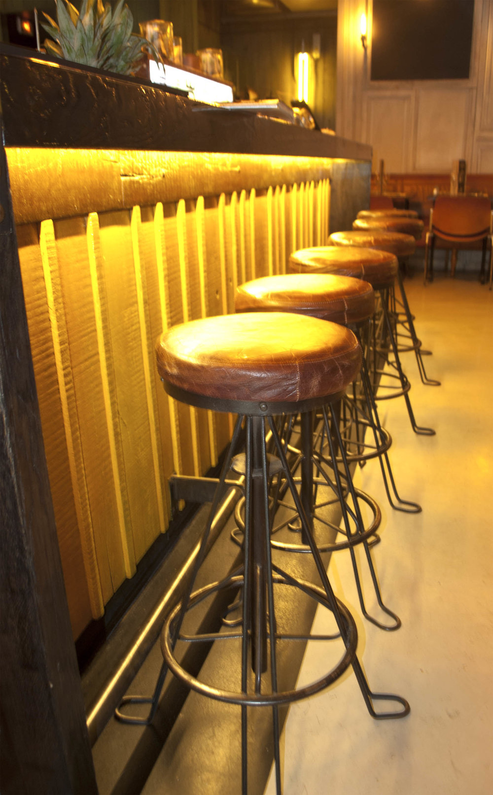 The under-lit rustic bar with worn leather bar stools
