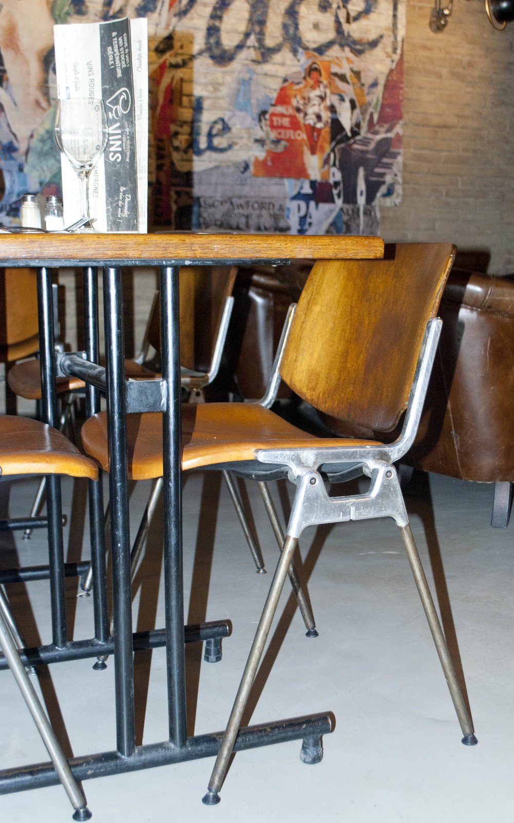 Industrial steel and wood chairs provide robust seating and clean lines. The flooring is kept very basic.