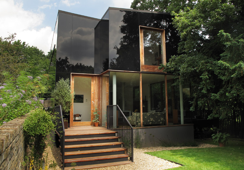 The Tree House by architect Ian McChesney. This spectacular house is located down a quiet lane in a conservation area in London, overlooking woodland. Clad in opaque black glass, the façade reflects, the sky, trees and gardens that surround it.