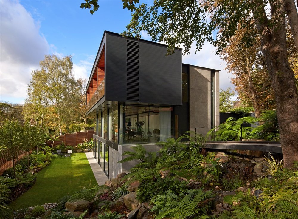 Fitzroy Park House in London, takes advantage of a sloping site in the Highgate Conservation Area, to create a large footprint with interlocking volumes and external terraces. The house has been carefully placed within its plot to preserve mature trees, which are then complimented with a lush new landscape design. The house won a RIBA London Award in 2015, and you can read more  here .