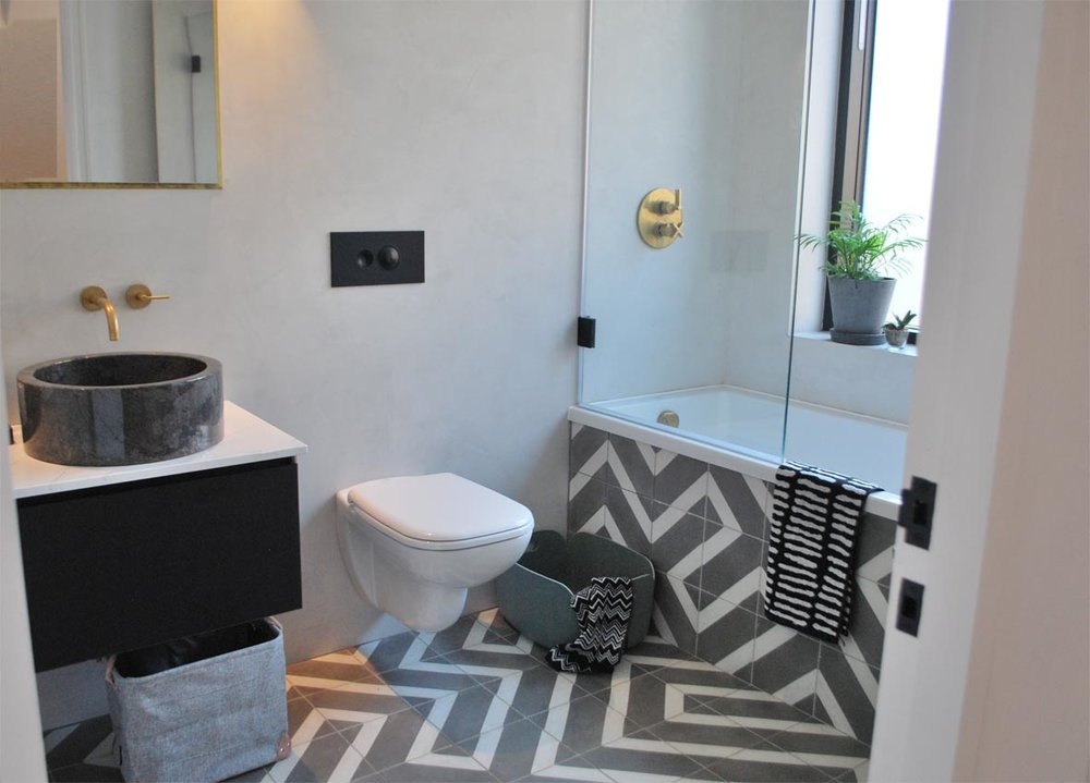 The Salon Inverse tiles by Bert and May run along the floor and retain the pattern up the side of the bath panel. The sleek polished plaster compliments the tile and keeps things simple on the walls, letting the floor take centre stage.