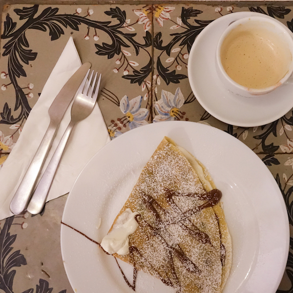 A yummy cappuccino with a nutella and mascarpone crepe for breakfast.