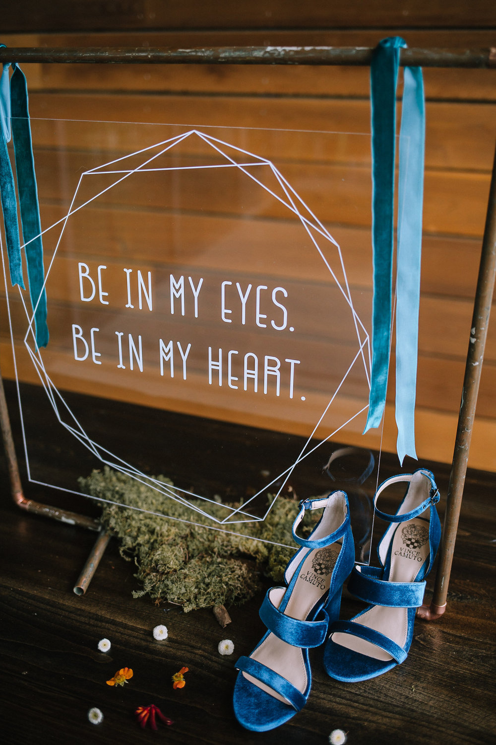 Vince Camuto turquoise velvet heels on a vintage farm table from Vintage Alley Rentals, featuring an acrylic sign by Purple Wagon Designs containing a Lumineers quote.