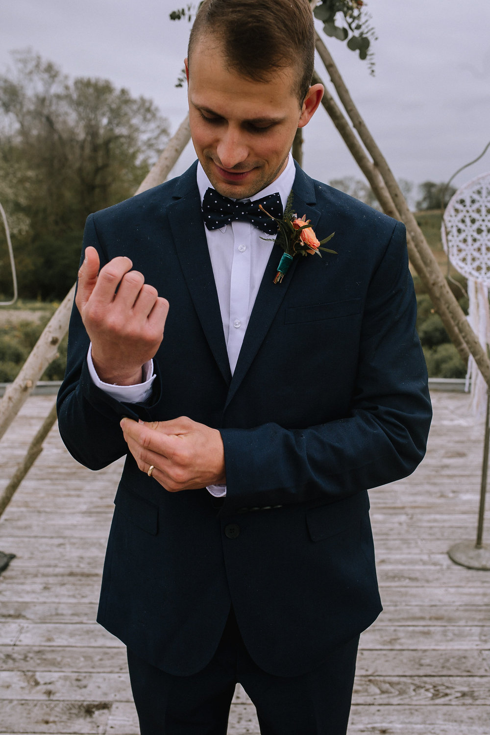 Groom wearing navy suit from H&M Man. Boutonniere from Community Flower Shop.