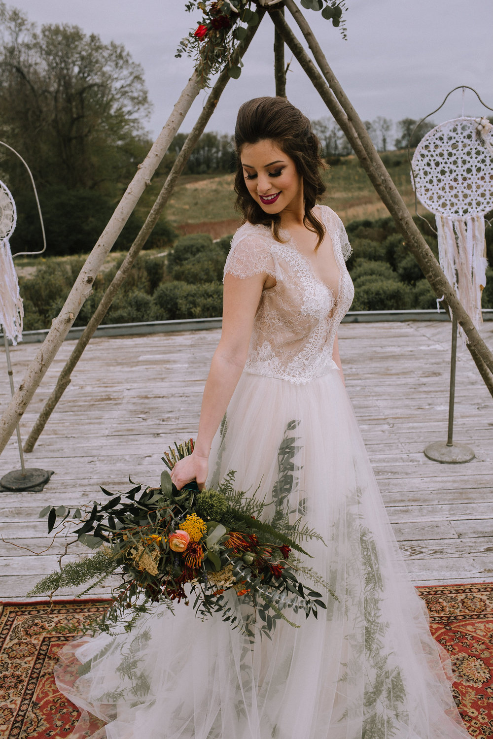 Melissa gown by Divine Atlier from Blanc de Blanc Bridal. Bohemian flower bouquet from Community Flower Shop at Chatham University Eden Hall campus wedding. Teepee and dreamcatchers from Vintage Alley Rentals.