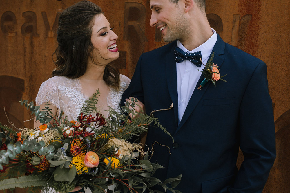 Bohemian wedding at Chatham University, Eden Hall Farm designed by Exhale Events. Bride's look from Blanc de Blanc Bridal, Melissa Gown by Divine Atelier. Groom's suit from H&M. Bridal bouquet and boutineer from Community Flower Shop.