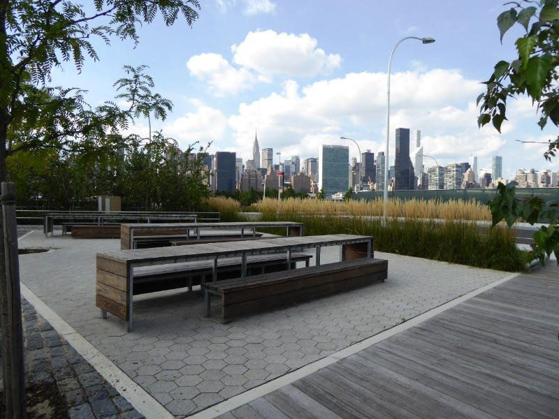 Picnic area along walkway from urban development to waterfront park with Manhattan on skyline
