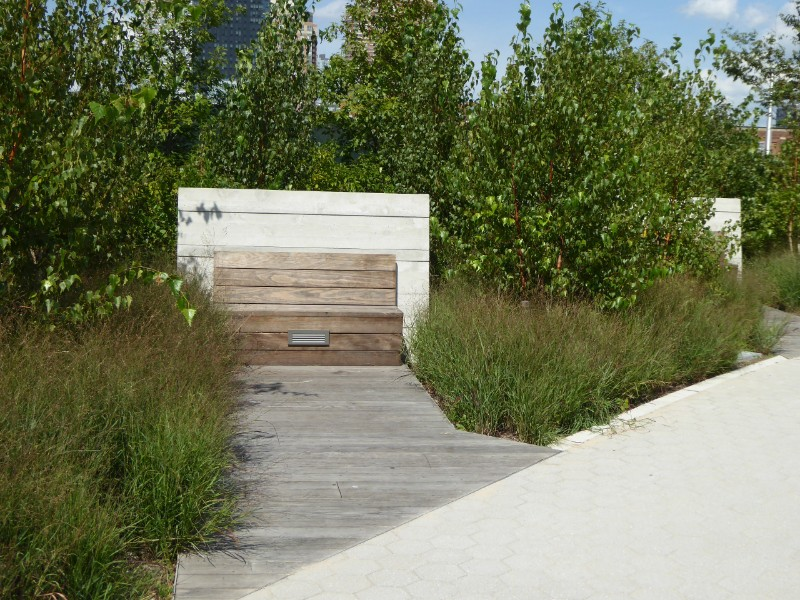 Seating adjoining waterfront path enclosed by planting
