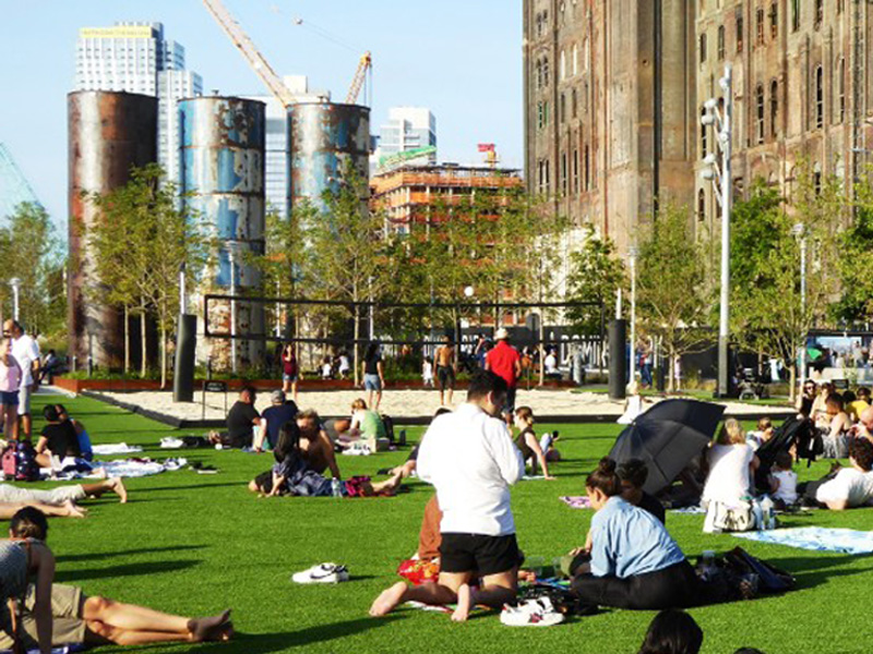 Lawn area with heritage tanks & Domino Sugar factory building beyond