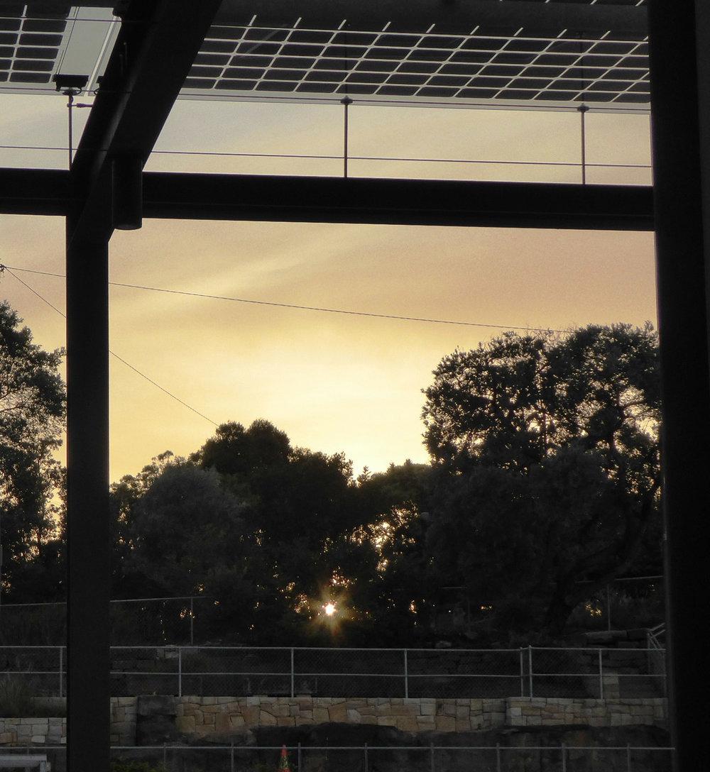 Sunrise through pergola with solar collectors