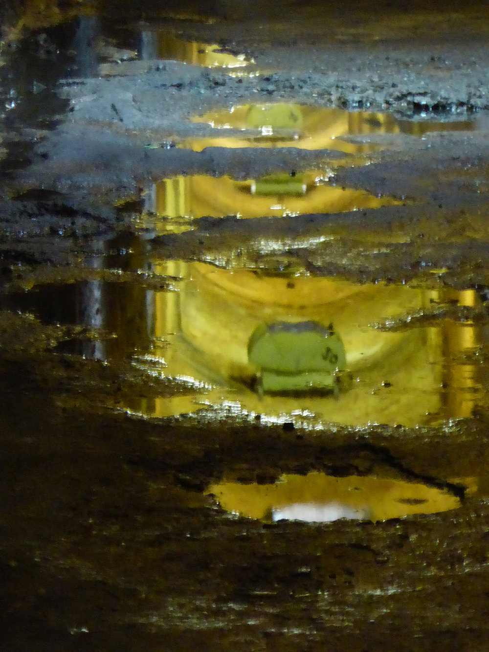 Underside of former coal chutes reflected in puddles on floor of tunnel