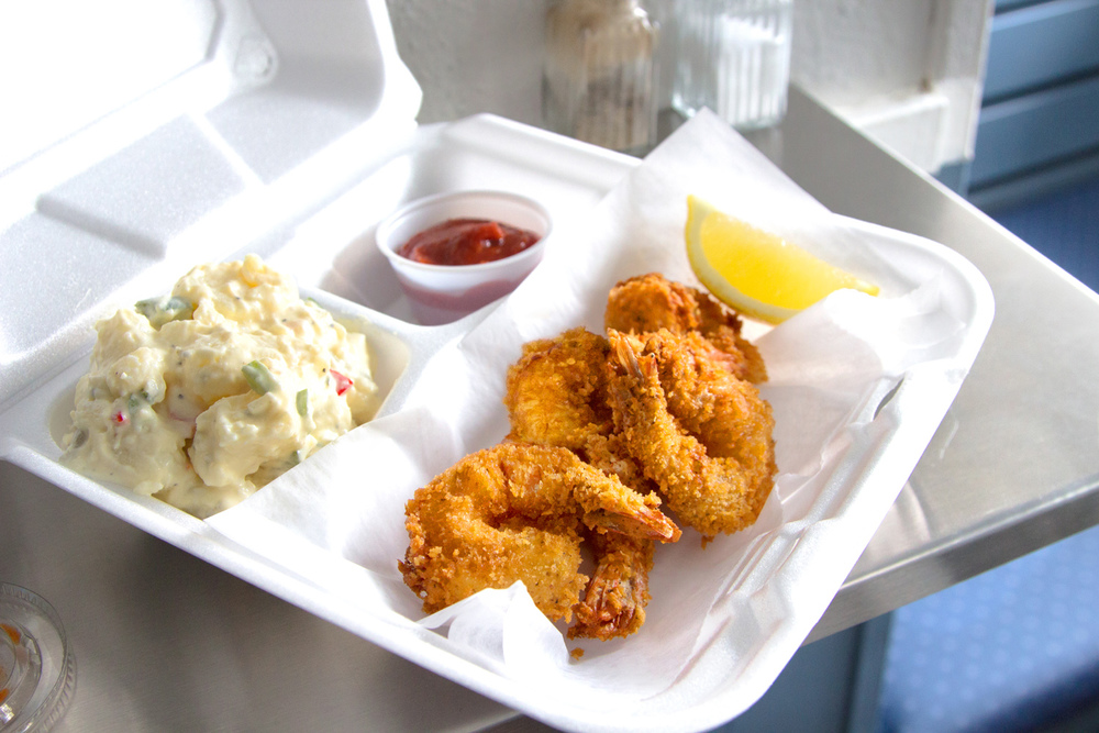 Fried shrimp with potato salad and cocktail sauce.