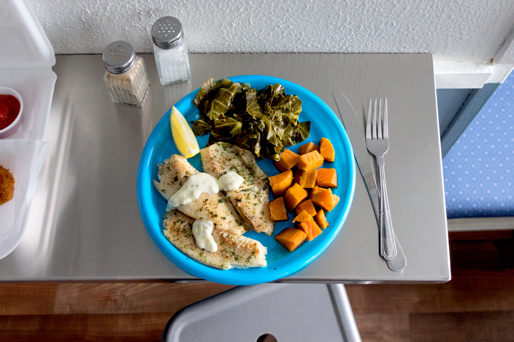 Broiled tilapia with collard greens and candied yams.