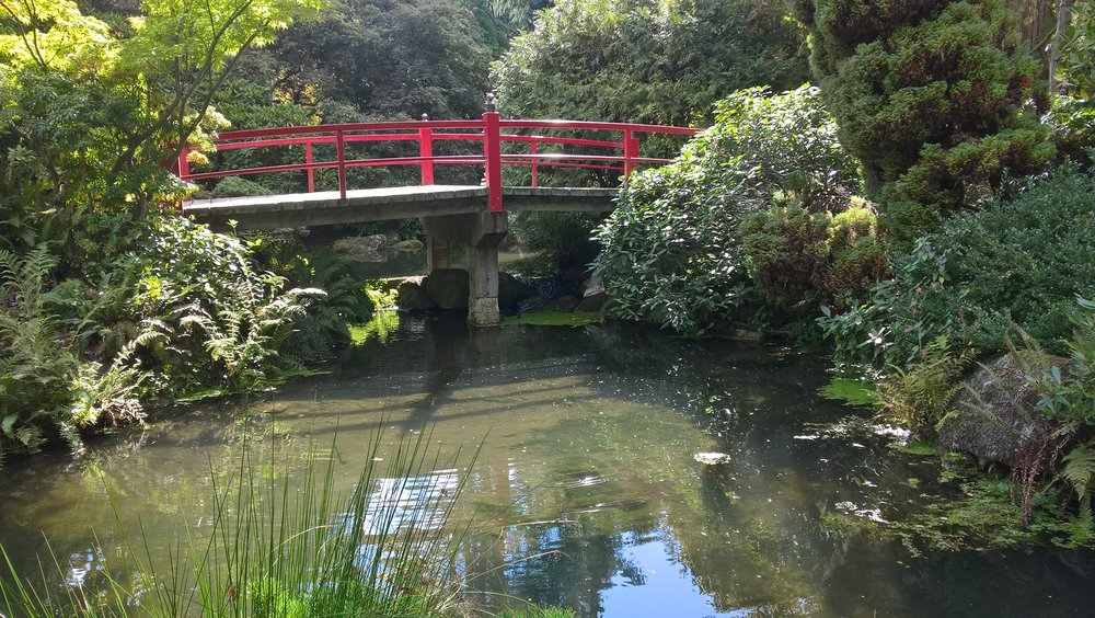 Large water features need to have a signature bridge.  This one is a quiet design with wornderful red railings.