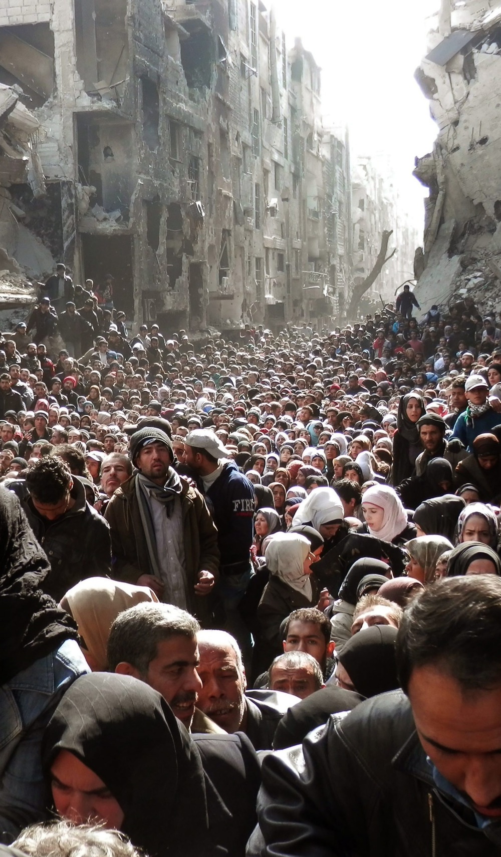 "american-radical :      6-2-midnight :      distilled-wisdom :      fnhfal :      War in Syria       One of the most haunting photos I've ever seen about the war in Syria. :(     this probably isn't even the front of the ""line"". factor that in     These are mostly Palestinian refugees in the Yarmouk refugee camp in southern Damascus, Syria. Before the revolution, it was home to some 160,000 residents, both Syrians and Palestinians but now it is home to around 7,000 Palestinian refugees. The city has been besieged by the Assad regime for more than two years and as of this year, there have been fights between regime forces and rebels and isis.  (x)"