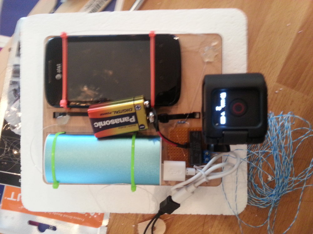 The top assembly of our Styrofoam payload, with tracking cell phone, backup battery, cut-down mechanism (aka wire burner), and GoPro