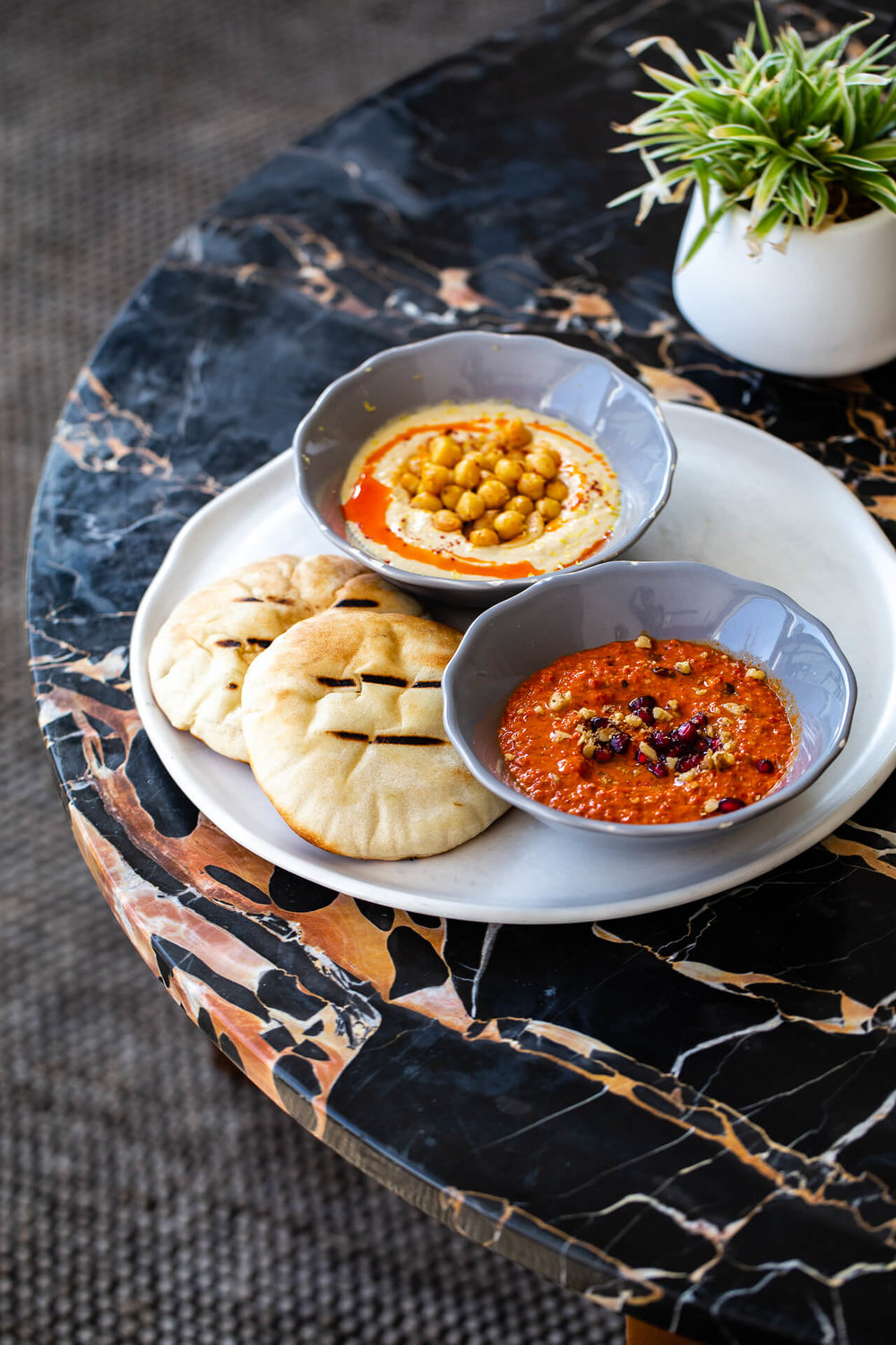 Dips and pitas arrive to satisfy the grumbly tummies of our wandering travelers at Rayla.