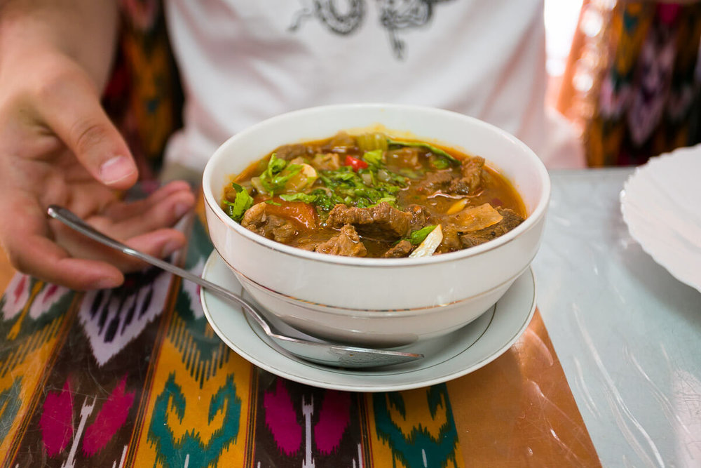 A rich and hearty bowl of  Shurpa  is filled with   cuts of lamb floating in lamb broth with onions and potatoes