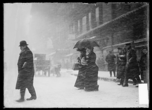 Two women under an umbrella crossing a street during a blizzard, Chicago, Illinois, February 4, 1903.