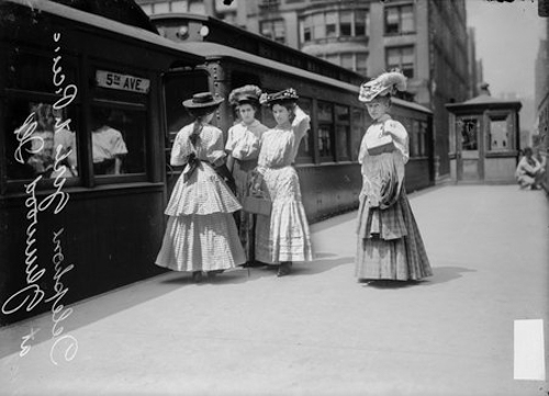 Four telephone operators standing on an elevated train platform on their way to a picnic