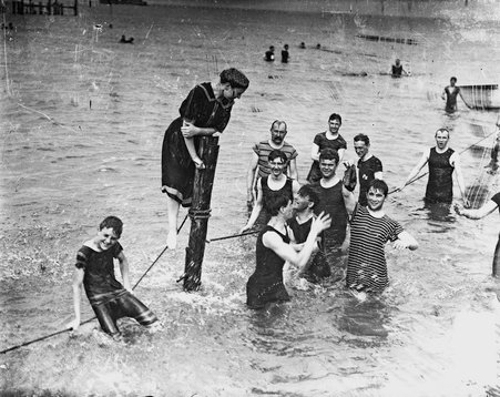 Image of a young woman standing on a rope line attached to a wood post with a group of young men in Lake Michigan near a beach in Chicago, Illinois.
