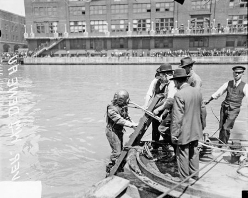 William Deneau, a diver in the Eastland disaster recovery efforts, standing on a ladder against a tugboat in the Chicago River in the Loop community area of Chicago, Illinois, circa August 28, 1915. Several men are standing on the tugboat. The Reid Murdoch Building is visible in the background.