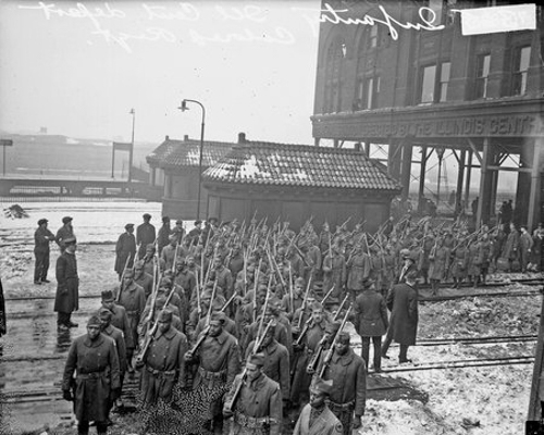 View from slightly above of the 365th Infantry, an African American infantry, marching with rifles at the Illinois Central Railroad Station. The station was located between Lake Park Court, East 12th Street and South Michigan Avenue in the Loop community area of Chicago, Illinois.