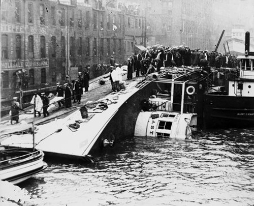 View of the SS Eastland a few hours after the ship overturned in the Chicago River, Chicago, Illinois, July 24, 1915.  Rescue crews are standing on the overturned ship.