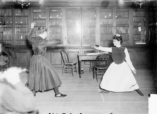 Women fencers, two women sparring in a room with desks and bookshelves