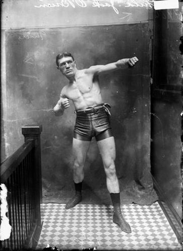 Full-length portrait of Jack O'Brien from Philadelphia, Pennsylvania, boxer, standing in front of a plain backdrop in a stairwell hallway at the Chicago Daily News building in Chicago, Illinois. He is wearing leather boxing trunks and punching with his right arm.