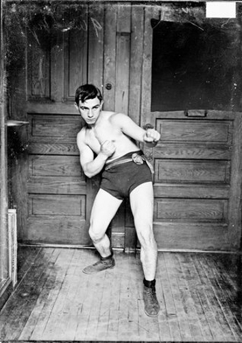 Portrait of Kid Herman, boxer, leaning back with left fist extended and right fist drawn back onto stomach in a room in the Chicago Daily News building in Chicago, Illinois.