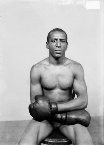 Portrait of Joe Gans, African American boxer, sitting in a chair wearing boxing gloves in a room in Chicago, Illinois.