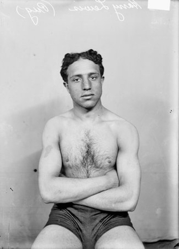 Three-quarter length portrait of Harry Lewis, pugilist, facing the camera, sitting in front of a light-colored backdrop in a room in Chicago, Illinois.