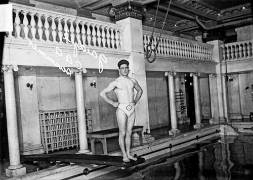 Full-length portrait of C. A. .A (Chicago Athletic Association) swimmer George Gaidzek standing on a diving board over an indoor pool in Chicago, Illinois. Two hoops attached to ropes are attached to a balcony railing in the background.