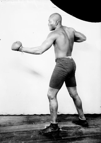 Full-length portrait of Jack Johnson, African American pugilist, standing in profile in a boxing stance in front of a light-colored backdrop in a room in Chicago, Illinois.