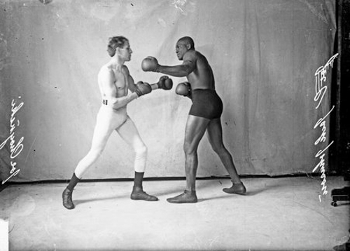 Full-length group portrait of Jack Johnson, African American pugilist, throwing a left hook at pugilist Joe Choynski, standing in front of a light-colored backdrop in a room in Chicago, Illinois.