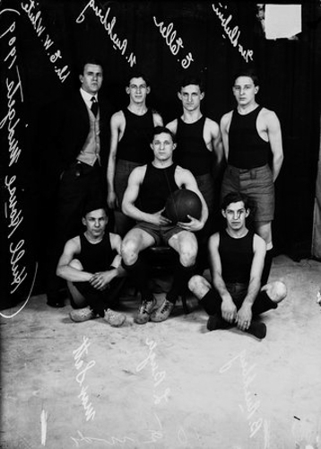 Group portrait of members of the Hull House Midgets basketball team, Chicago, Illinois, 1909. Sitting in the foreground (left to right): Max Scott, Louis Berger (in a chair, holding a basketball), and Bernard Ruekberg. Standing in the background (left to right): coach Dr. E. W. White (wearing a suit), Nathan Ruekberg, E. Ellen, George Dubin.