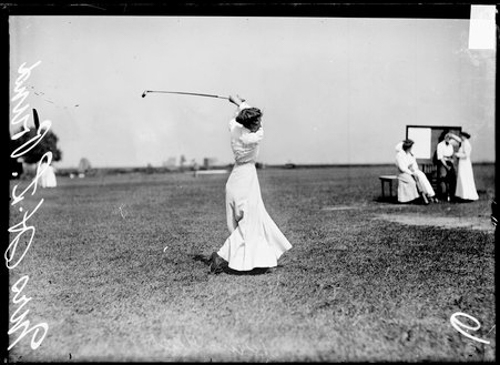 Informal full-length portrait of Mrs. H. L. Pound, golfer, following through after swinging a golf club, standing on the grounds of an unidentified golf course in or near Chicago, Illinois. Two women are standing and one woman is sitting in the background.