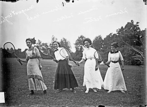 Portrait of Tennis players Ms. Margaret Wylie, Ms. Florence Hass, Miss Amanda Falker and Ms. Florence Felton holding their racquets in their right hands, leaning to their right, posing on the grass at Washington Park in Chicago, Illinois. Miss Falker is an African American athlete.