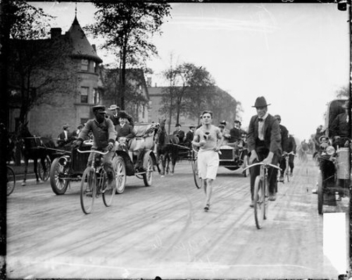 Informal full-length portrait of Metzner, a runner, running on a street in Chicago, Illinois, surrounded by men riding bicycles and riding in automobiles and a horse-drawn wagon. An African-American man is riding a bicycle in the foreground. Buildings are visible in the background.