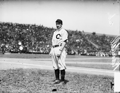 Informal full-length portrait of baseball player Newt Randall of the National League's Chicago Cubs baseball team, standing in foul territory next to the first baseline on the field at West Side Grounds, located between West Polk Street, South Wolcott Avenue (formerly Lincoln Street), West Taylor Street, and South Wood Street in the Near West Side community area of Chicago, Illinois. Crowds are visible in the bleachers in the background.